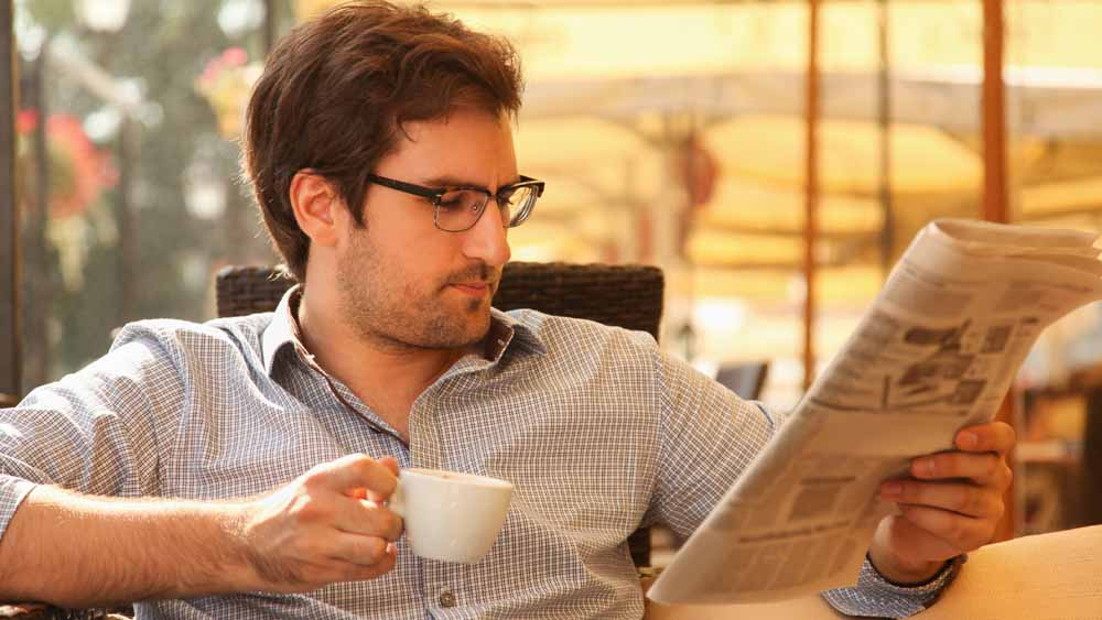 Handsome young man enjoying in cafe reading newspapers and drinking coffee.