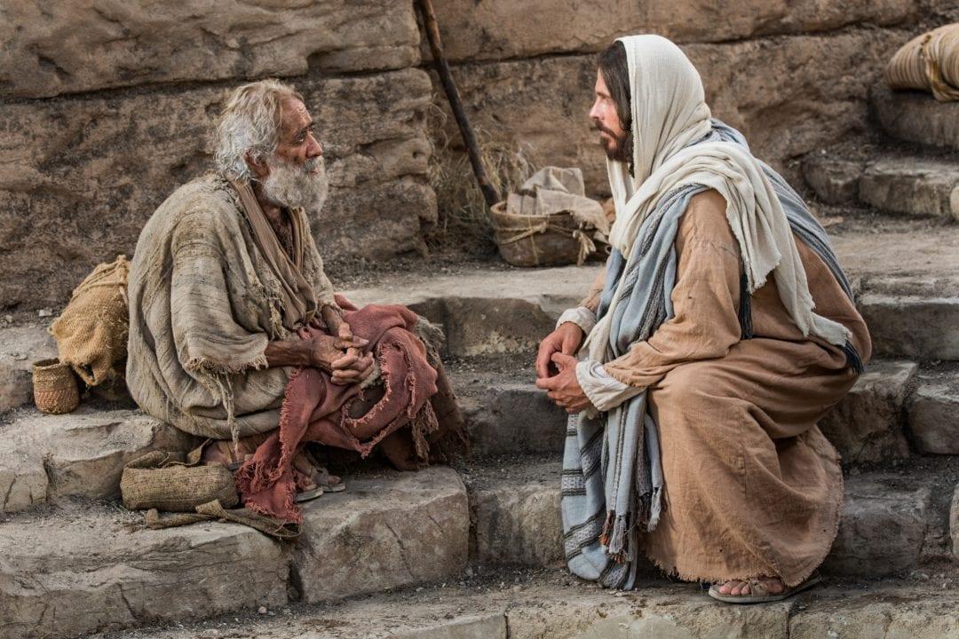 Escena de película en que Jesús habla con un pobre paralítico