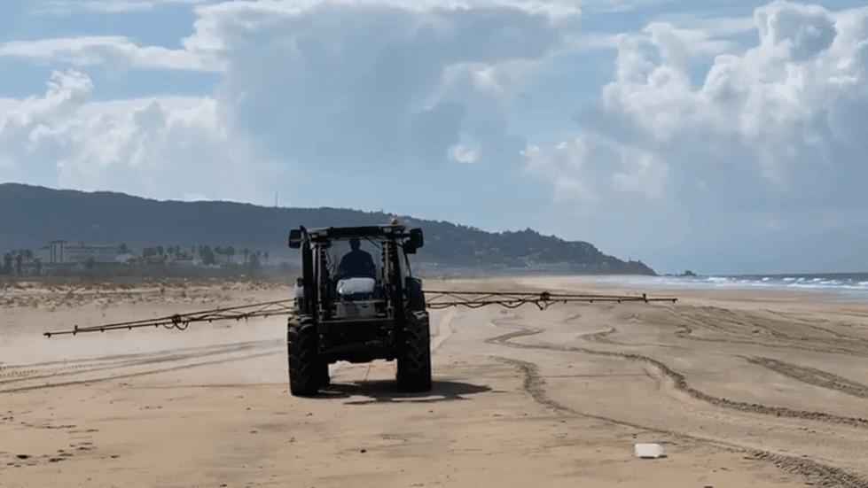 Un tractor rocía lejía en la playa de Zahara de los Atunes