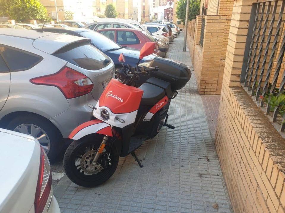 Moto eléctrica de ACCIONA Movilidad mal aparcada en una calle de Castilleja de la Cuesta