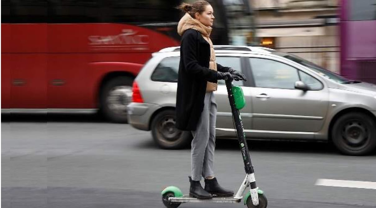 Una mujer circulando con un patinete eléctrico